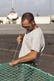 Pêcheur reprisant un filet de pêche