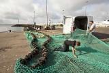 Pêcheurs réparant un filet de pêche